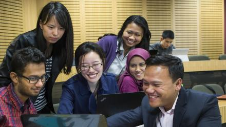 Dr Vinh Lu (right) with ANU management students. Photo by Stuart Hay.