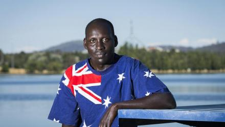 ANU PhD candidate Atem Atem in the Australian flag t-shirt he wore when he was racially abused next to Canberra's Lake Burley Griffin. Photo: Stuart Hay.