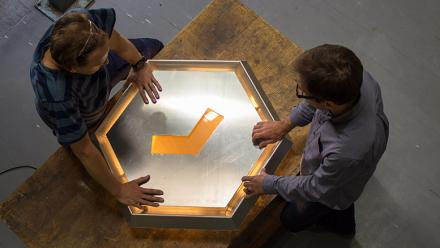 Sean Booth (left) and Rohan Nicol working on the 'cupped hand' section of the Wright Hall crest. Photo by Adam Spence.