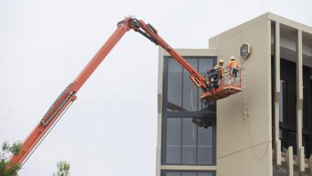 Installing the crest on Wright Hall. Photo by Lannon Harley.