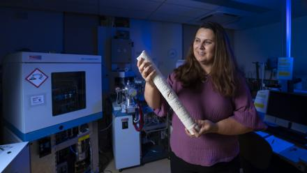 Professor Nerilie Abram, from the ANU Research School of Earth Sciences, holds a coral core used to research past climates and climate change, photographed in her lab.  (Lannon Harley/ANU).