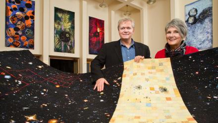 Professor Brian Schmidt AC and Valarie Kirk with Kirk's The Schmidt Tapestry, 2012-13, University House collection.