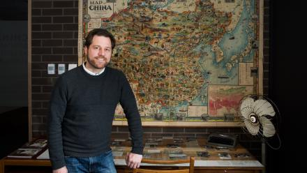 Exhibition curator Dr Olivier Krischer in front of John Diakoff's pictographic map of the people and topography of the Chinese Republic, Northern Trading Company and Mr VF Yao-hsiun, Harbin, 1931.