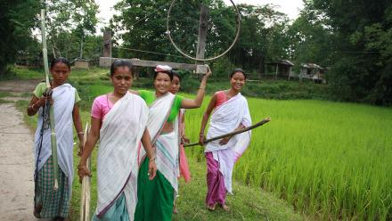 Artisans walking with a handloom in Assam. Photo: Impulse Social Enterprises.