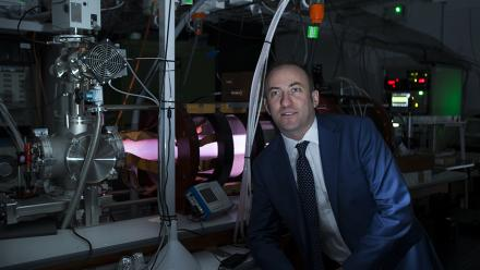 Dr Cormac Corr, Director of the Australian Plasma Fusion Research Facility at ANU, in front of a high-power linear magnetised plasma machine called MAGPIE I, which will support research in advanced fusion materials. Photo by Stuart Hay.