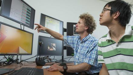Associate Professor Matthew Hole and PhD candidate Zhisong Qu in the virtual control room for overseas fusion experiments in the ANU Research School of Physics and Engineering. Image: Stuart Hay.