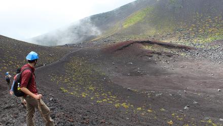 A student studies the remnants of the fissure which formed the Mount Hoei cinder cone on the flanks of Mount Fuji