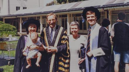 Amy Chin-Atkins and David Atkins at graduation, with baby Liam, ANU Chancellor Professor Peter Baume and Mrs Jenny Baume. Photo: supplied.