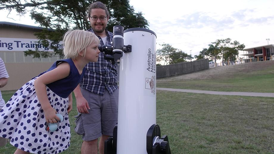 Dr Brad Tucker shows a would-be astronomer how to focus on the Moon during an early evening event in Rockhampton. Photo by Pamela Lourandos.