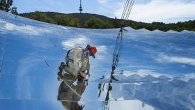 Felix Venn, one of the researchers involved, on the ANU solar thermal dish. Image: Stuart Hay