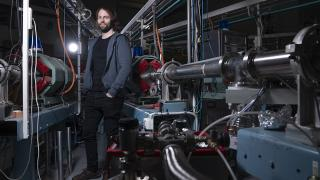 Lindsey Bignell next to the ANU's 14UD particle accelerator at the Heavy Ion Accelerator Facility, which he uses to understand the response of the dark matter detector to different types of particles. Photo: Lannon Harley
