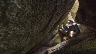 Jesse Wallace in a cave tracking bogong moth migration. Photo by Lannon Harley.